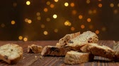 cânhamo : italian cantucci with almond and cranberries falls on a wooden surface against the background of Christmas light strings Stock Footage