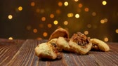 orzechy włoskie : Italian Fig Cookies Cucidati falls on a wooden surface against the background of Christmas light strings, buccellati, traditional sicilian pastry