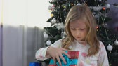 pajamas : Little girl in pajamas handed a Christmas present near the Christmas tree on Christmas morning Stock Footage