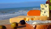 finomság : Knife spreads soft cheese on bread on a wooden board in front of the Surf of the Atlantic Ocean Stock mozgókép