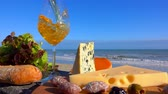 normandia : Romantic picnic with Normandy cheese and snack on a wooden board in front of the Surf of the Atlantic Ocean. White wine is poured into a wine glass