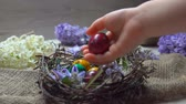 decorative rabbit : Childs hand lays festive colored egg in in the Easter nest