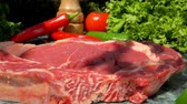 butchers : Veal steak gently lowered onto a green marble table. Still life of meat, herbs, spices and vegetables