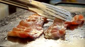 hearty : Cook turns bacon with metal tongs on the hot surface of the stone grill