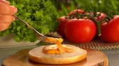 салат латук : Spoon smears the sauce onto a hamburger bun. On the table prepared products for burgers