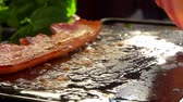 oldal : Cook turns bacon with metal tongs on the hot surface of the stone grill
