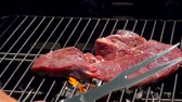 перчинка : Cook lays the steak with a metal fork and spatula on the grill grate over an open fire
