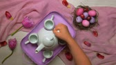 codorna : Womens hands put a tray of tea on the Easter table in pink tones and spill the tea into cups