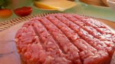 бекон : Raw beef burger lies on a wooden board on the table. Panoramic camera movement.