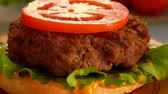 бекон : Rings of chopped onions falls on a hamburger. On the table prepared products for burgers