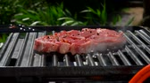 biber tanesi : Cook lays a raw pork steak with a kitchen spatula on a hot grill over an open fire Stok Video