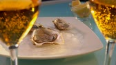 устрица : On the table stands a sparkling wine against the background of a plate of oysters on ice and bowls of lemon
