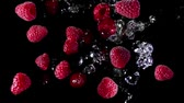 jam : Ripe raspberry fly with water to the camera on a black background Stock Footage