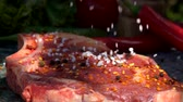 Coarse salt falls on the veal steak in slow motion. Still life of meat, herbs, spices and vegetables Vídeos