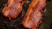 Close-up camera movement near of a two bacon strips hissing and frying on the hot stone surface