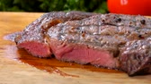 Chef cuts the finished juicy beef steak on a wooden board with a large knife and fork Vídeos
