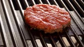 бекон : Smoke rises above the cutlet on a hot grill. Tasty beef burger flipping on the grill.