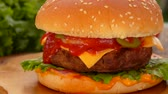Fresh tasty burger lies on the table on a wooden board. Panoramic camera movement.