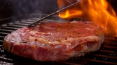 перчинка : Cook presses the steak on the hot surface of the grill with a spatula on over an open fire.