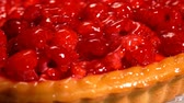 Fresh raspberry pie covered with jelly is putting on the table