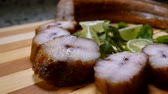 ramper : Pieces of smoked eel lie on a wooden board. Panoramic camera movement. Vidéos Libres De Droits