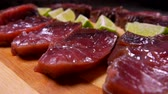 biodiverzitás : Slices of lightly salted tuna and lime are lying on a bamboo cutting board. Panoramic camera movement.