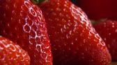Drop of water dripping on a large ripe strawberries. Slow-motion drop in extreme close-up