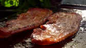 paprika : Two strips of raw bacon are roasted on the hot stone surface of the grill