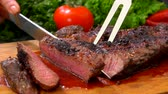 paprika : Chef cuts the finished juicy beef steak on a wooden board with a large knife and fork Stock mozgókép