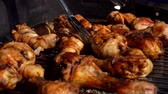 thighs : Chicken legs and wings turned with metal tongs on the grill in the open air Stock Footage