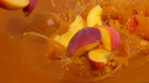 mouillé : Slices of peach fall into juice with beautiful splashes in slow motion