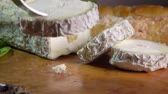 mouldy : Fork lifts a piece of cheese. Goat cheese with blue-grey mould has a long straw that traverses the middle.