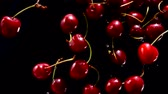 Ripe cherries fly on a black background closeup in slow motion