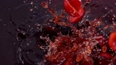 Ripe cherry fall into juice with beautiful splashes in slow motion Vídeos