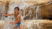 rodeln : The boy repeats the movement of dance for the coach. Boy is dancing standing on the rocks on the pool