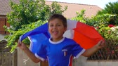sport kleding : Boy fan of the French national team jumping for joy with a French flag in his hands. Stockvideo