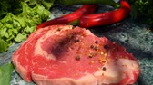перчинка : Mixture of spices falls on the veal steak in slow motion. Still life of meat, herbs, spices and vegetables
