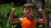 campeão : A boy in an orange shirt shows his biceps and shows OK. Stock Footage