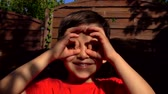 şans : Little boy makes binoculars gesture with his fingers Stok Video