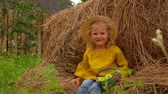 Cute little girl in a straw hat sits on a haystack with a basket of apples