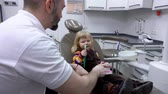 Little girl learns from the dentist how to brush teeth on a model of the jaw Стоковые видеозаписи