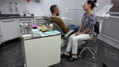 ホワイトニング : Patient tells the dentist about his problems while sitting in a chair