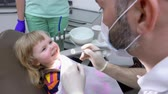 ortodôntico : Small child smiles and opens his mouth so that the dentist can check his teeth. Dental clinic Stock Footage