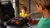 veranda : Boys cooks cutlets on the grill.