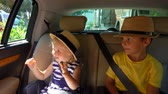 seat belts : Little children in hats travel by car Stock Footage