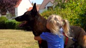 sheepdog : Little blond blue-eyed girl caresses a Belgian shepherd dog