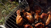 ohnivý : Chicken legs and wings turned with metal tongs on the grill in the open air Dostupné videozáznamy