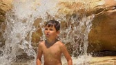 aquático : The boy repeats the movement of dance for the coach. Boy is dancing on the rocks on the pool