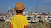 sailboat : Little boy in a straw hat is looking on the yacht port