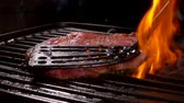 перчинка : Spatula presses the steak on the hot surface on the grill with over an open fire